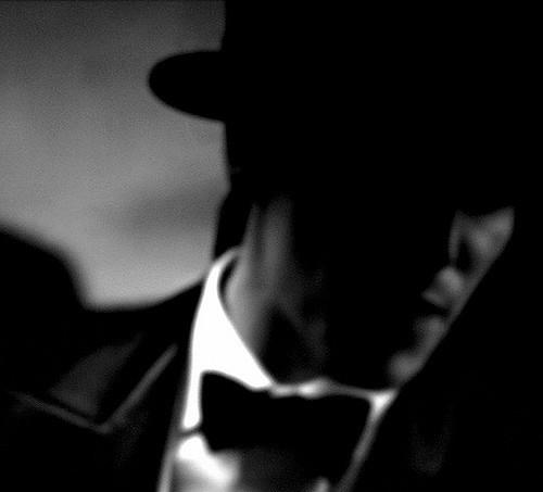 Un homme en costume nœud papillon, en noir et blanc.