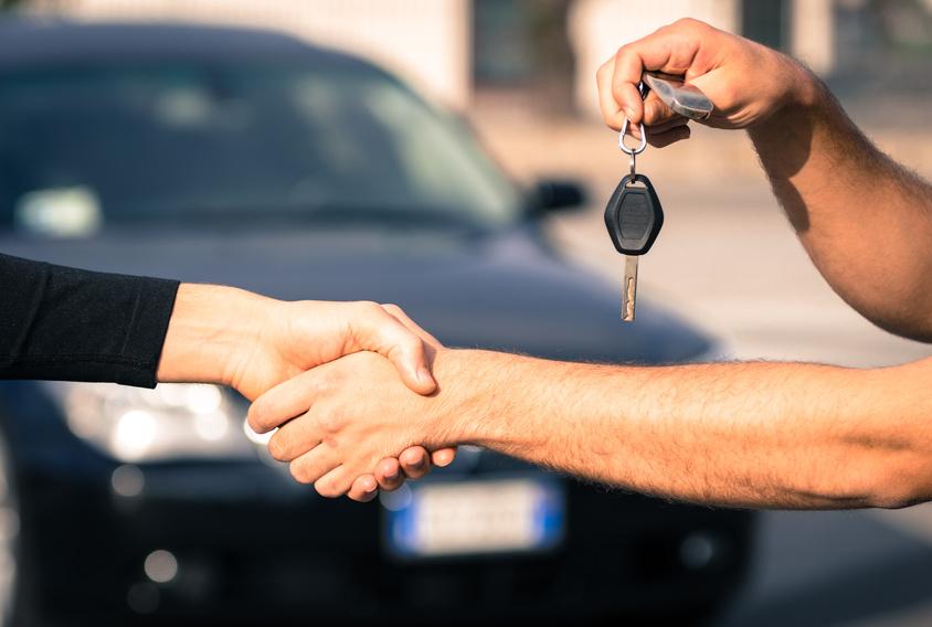 Deux personnes se serrent la main devant une voiture.