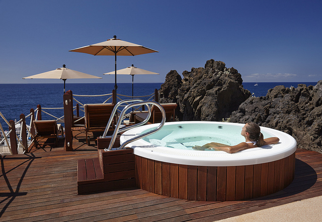 Spa en extérieur sur une terrasse d'hôtel en bois avec vue sur la mer.