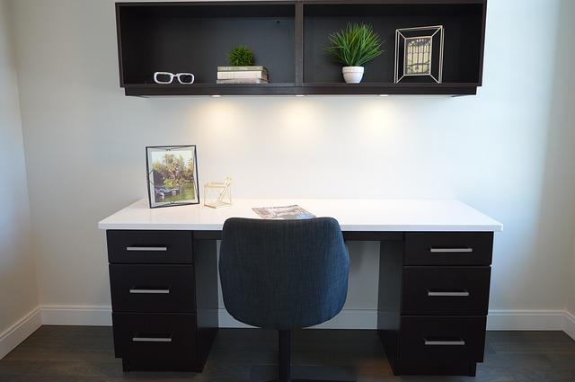 Bureau avec une étagère murale au-dessus.