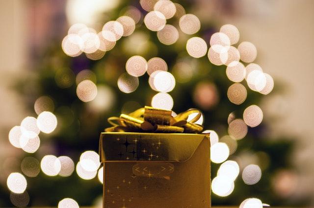 Une boite de cadeau devant un sapin illuminé.